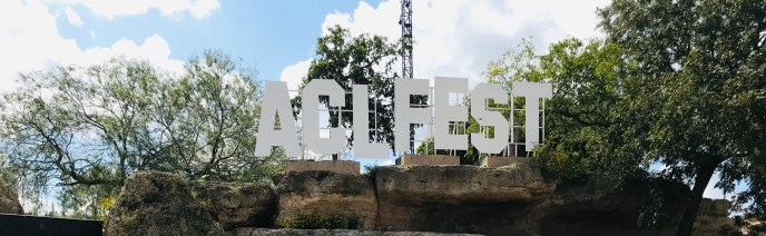 """The letters """"ACL FEAST"""" spelled out in white over a rock."""