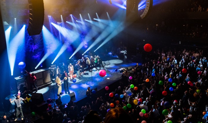 People on stage are singing and dancing. The crowd is playing with a dozen balloons, which are all different colors and sizes.