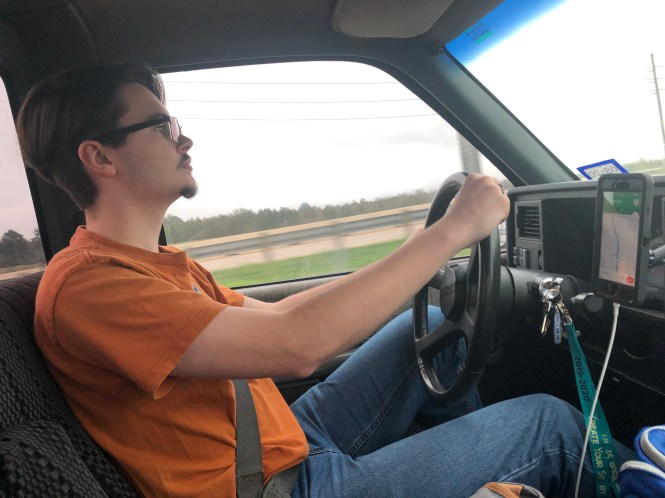 A boy in an orange shirt pilots a vehicle.