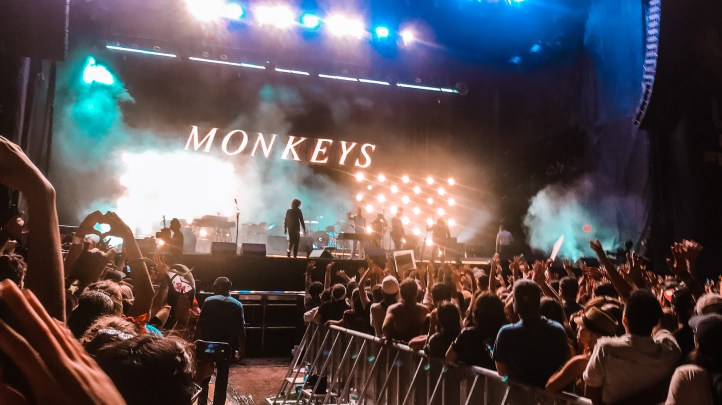 """crowd gathers around a stage blaring bright lights and '"""" Monkeys"""" spelled out on stage"""