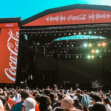A large crowed gather around a stage and a large screen for music artist.