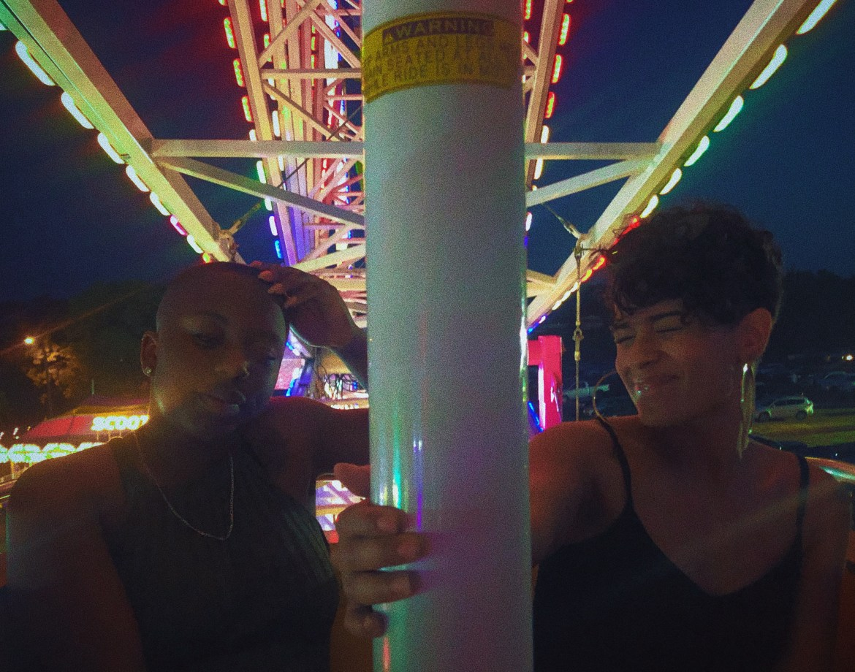 Two friends on a ferris wheel at an amusement park.