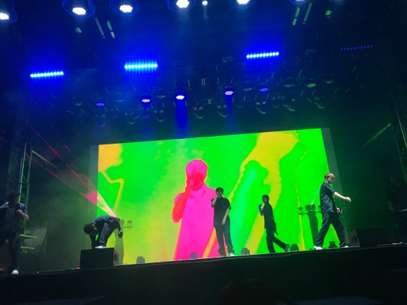 Five men performing on a colorful lit up stage