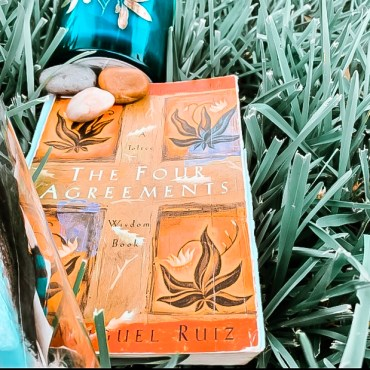 orange book cover on grass with rocks and a candle