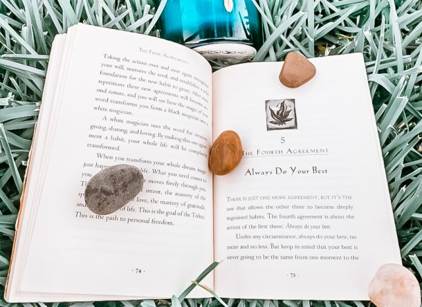 open book with a blue candle and rocks