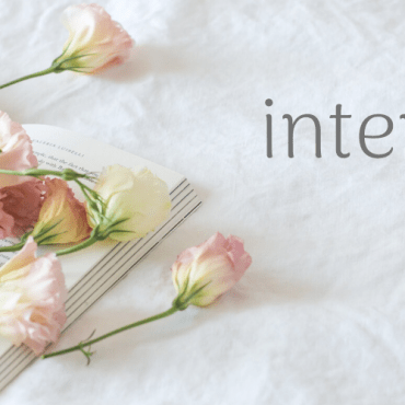 """Light pink flowers laying across a book. Next to it, the words """"international women's day"""" in a curvy, gray font."""