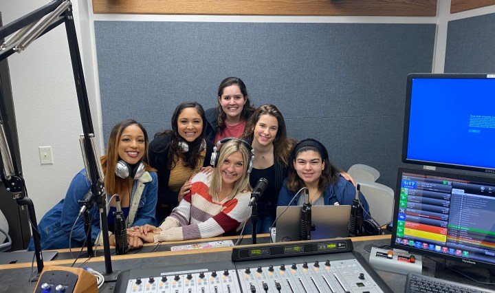 Six female KTSW Sports staff members gather around the mics, some with headphones on, some without, as they smile for the camera after a successful episode