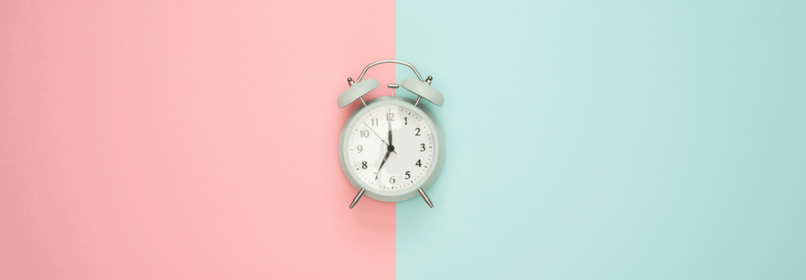 An alarm clock on a light pink and mint green background