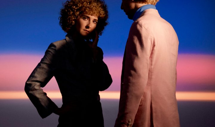 In front of a blue and purple background, Alaina Moore and her partner, Patrick Riley are standing but not looking at each other.