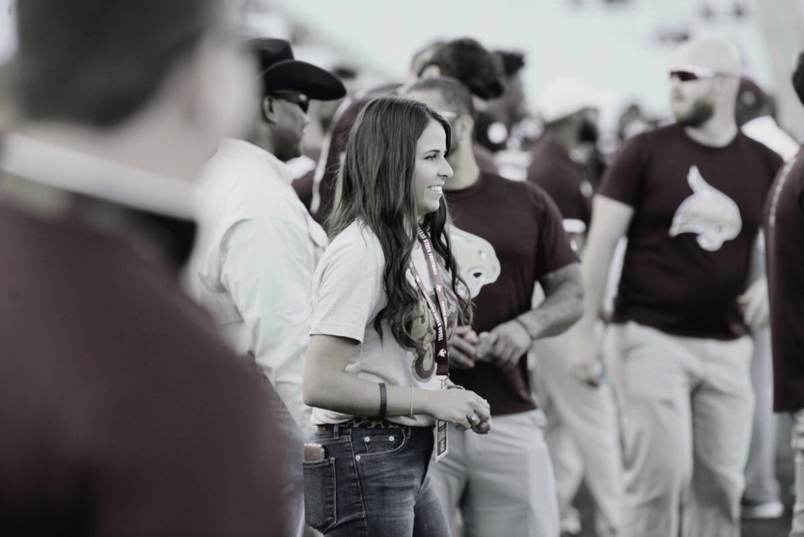 : Black and White photo of Haleigh Blocker smiling on the sidelines with other staff members in the background.