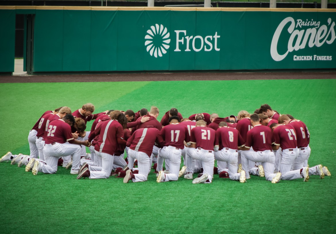 Texas State Baseball Team dressed in maroon uniforms takes a knee in a circle in the grass in left field