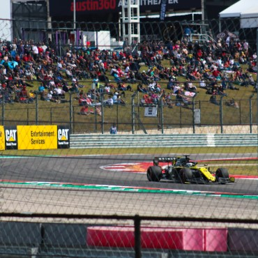 A yellow and black Renault F1 car on the exit of a corner at the Circuit of The Americas