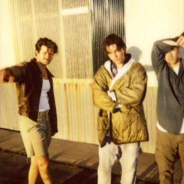 The visual is a photograph of the three band members.