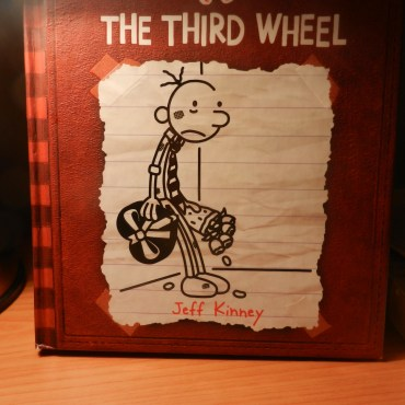 """""""Diary of a Wimpy Kid"""" red book cover on a desk."""
