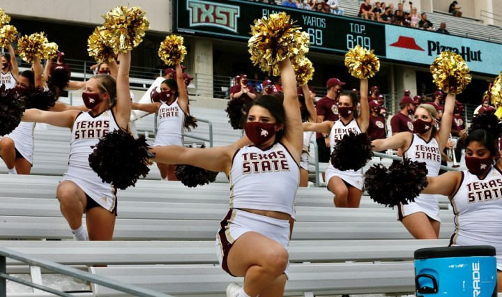 The Texas State Cheerleaders dancing at the SMU game in the stand.