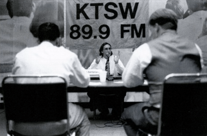 Old image of two people having a debate and a moderator under a KTSW sign. Description: From the 1997 SWT Yearbook.