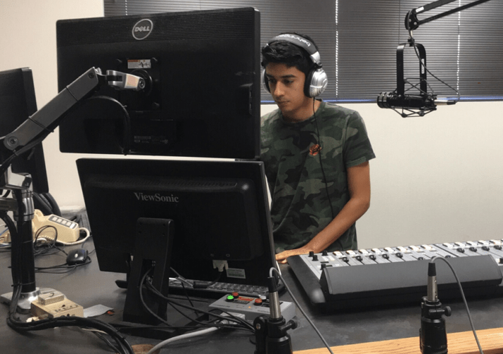 Man in front of the computer with headphones and microphones.