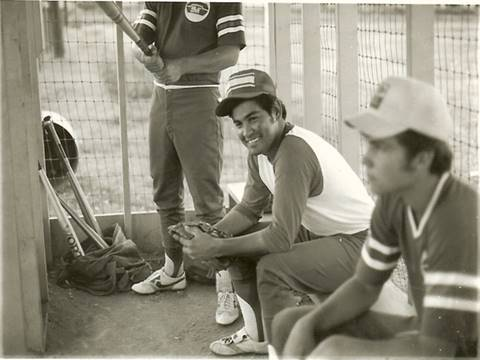 John in baseball uniform on a bench.