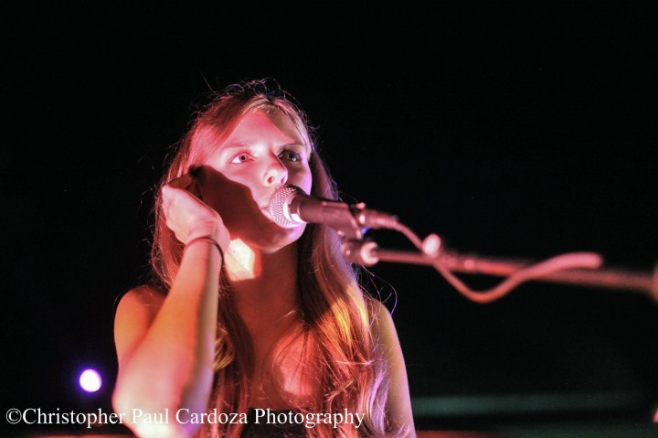 Girl with pink light on her singing at a mic