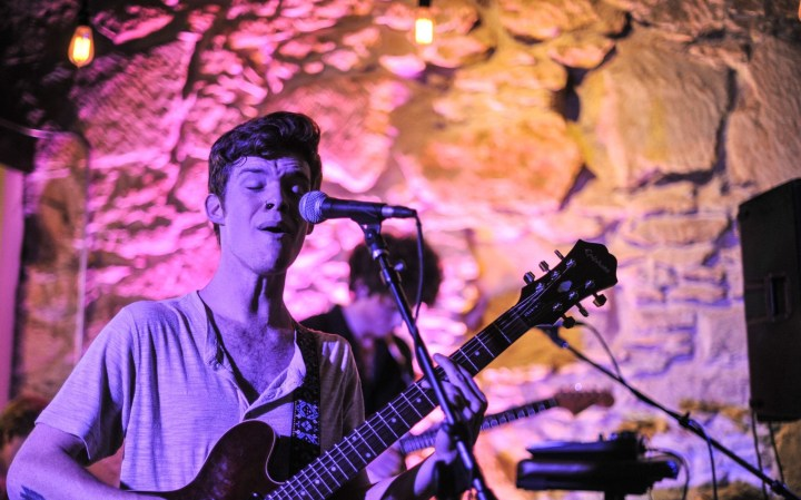 Man in purple light holding guitar while singing at a mic.