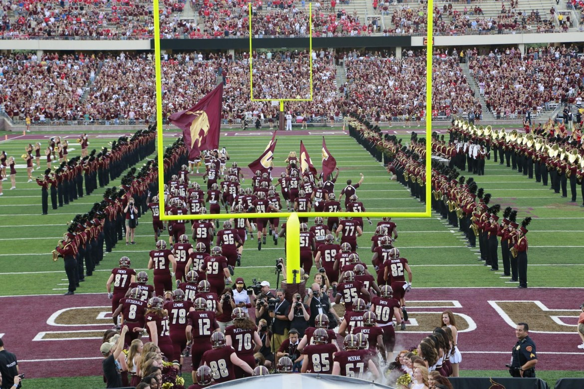 Texas State football players run onto the field inside Bobcat Stadium with the Texas State band and cheer squads tunneling them towards the goalpost as fans fill the stands.