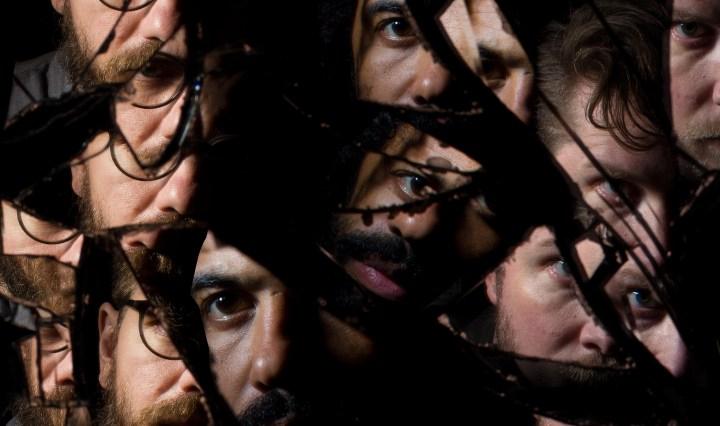 Band members look into broken glass.
