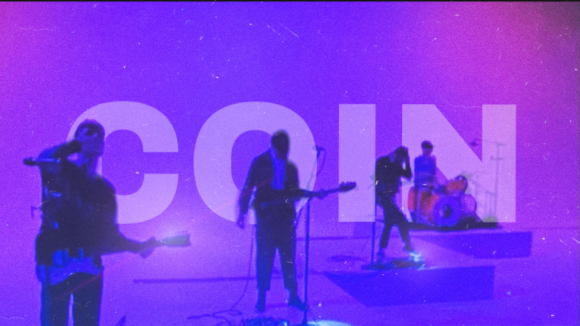 """COIN under purple and blue lights with """"COIN"""" typed behind them"""