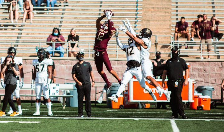 Texas State wide receiver Marcell Barbee jumps and catches a pass with two Appalachian State defenders behind him.