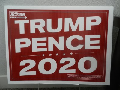 A Trump-Pence sign leans against a wall.