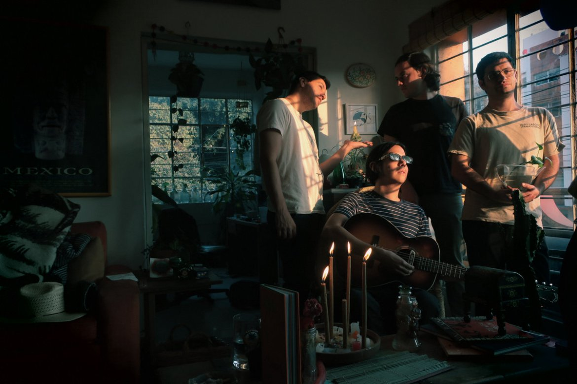 This is a group photo of the four members of Los Blenders standing in a dim room, next to a window with the sunlight shining on their faces.