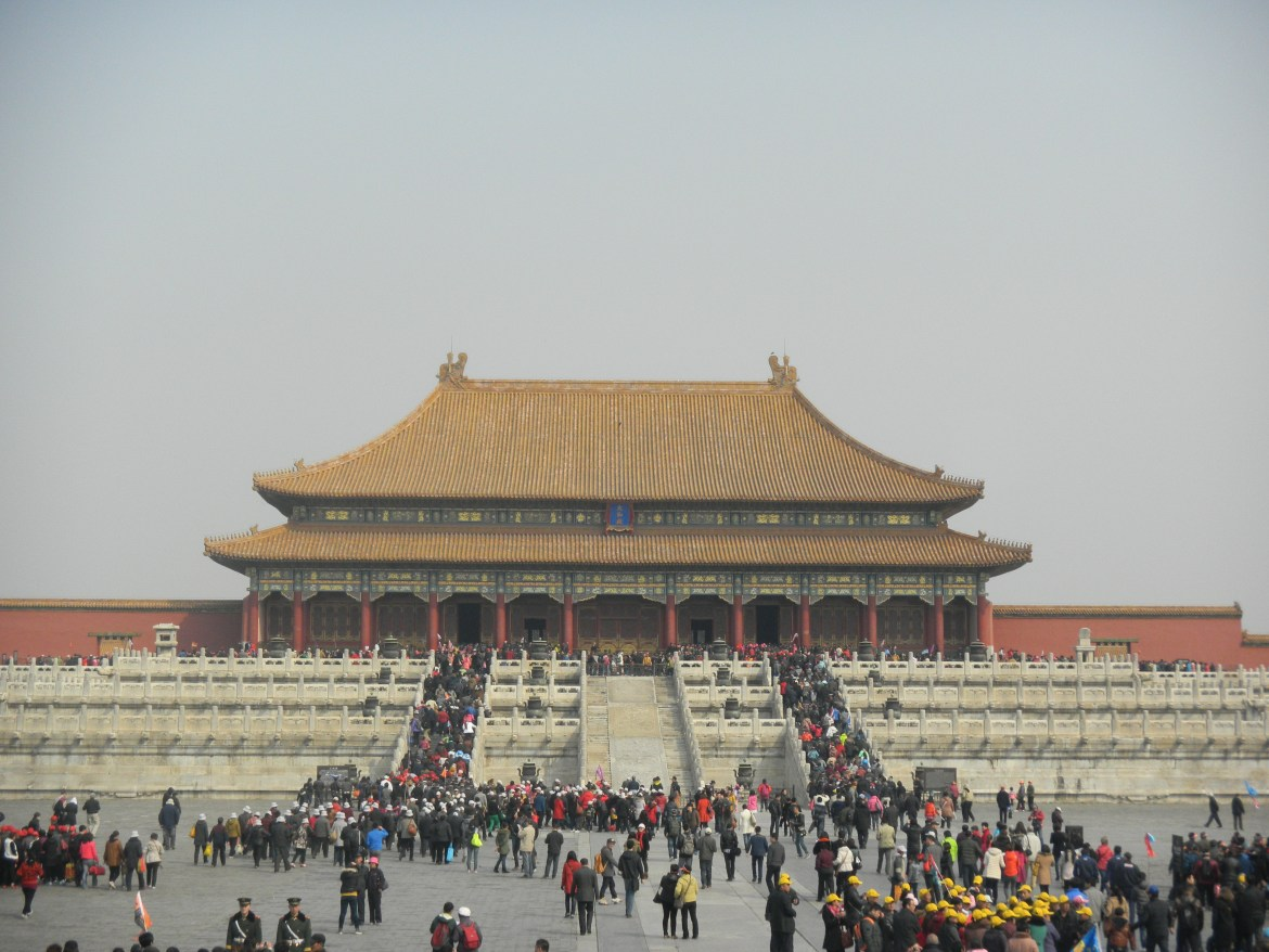 A large, building with Chinese architecture. Many people crowd the front to enter.