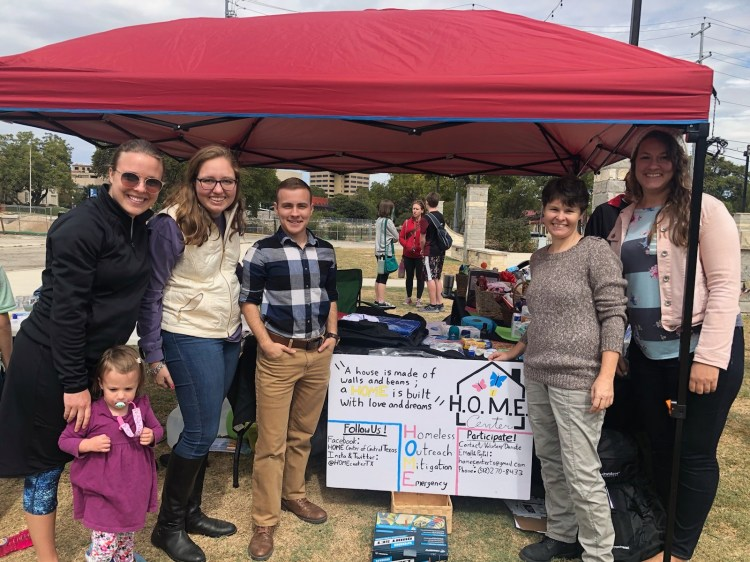 Volunteer members pose beside booth at outdoor event.