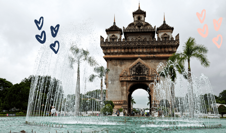 A small tower in the middle of fountains and trees with hearts drawn on.