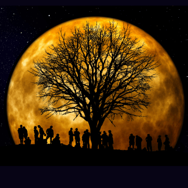 Image of a large muted yellow moon with the black silhouettes of people seen in the foreground. Placed on a solid black background.