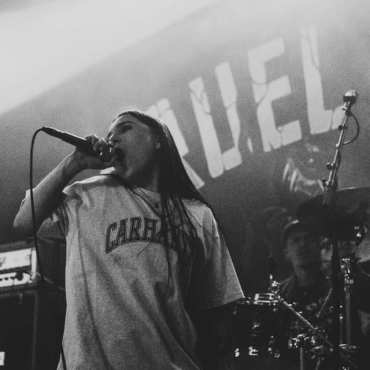 This is a black and white photo of the lead vocalist of Caged Existence singing at a show.