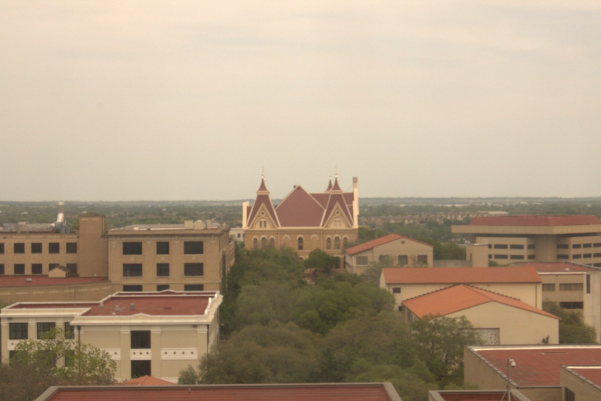 Photo of Old Main taken from Alkek Library on a foggy evening.