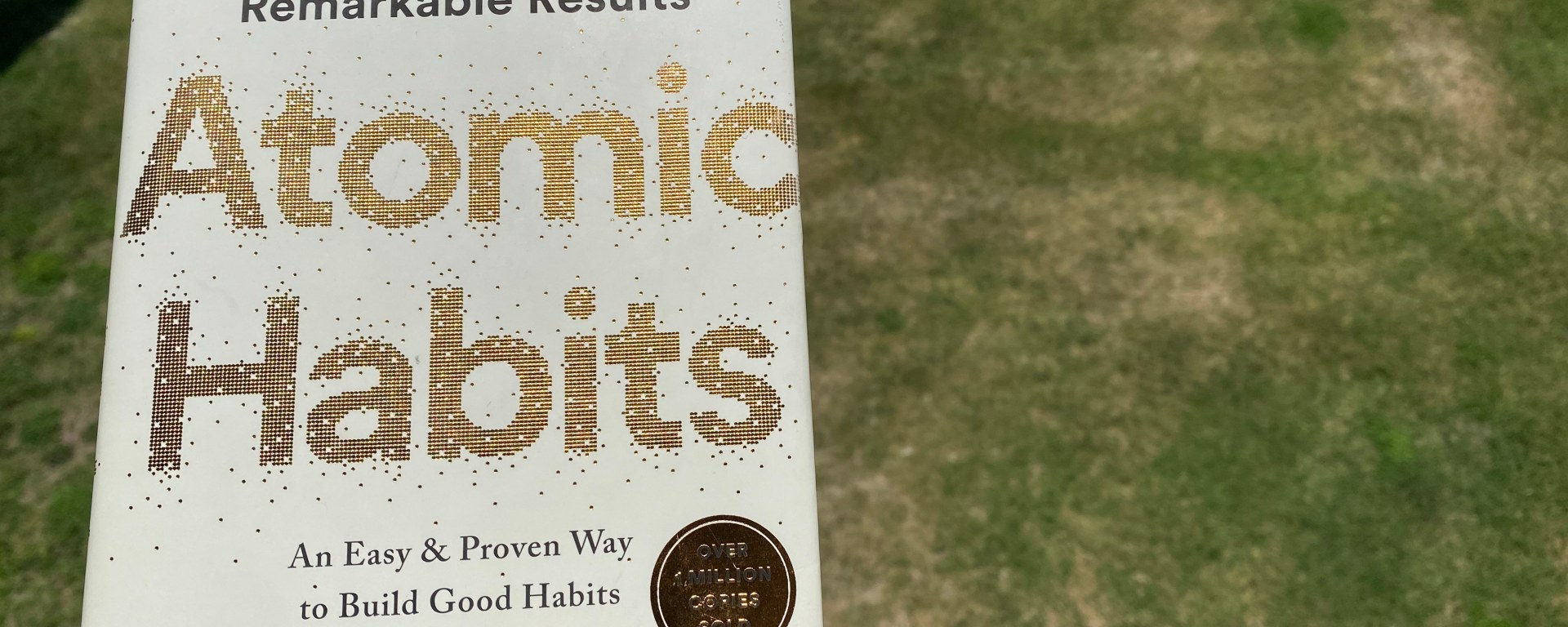 """Book cover for """"Atomic Habits"""" by James Clear with green grass in the background."""