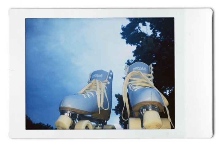 Photo of light blue and yellow roller skates with the sky in the background