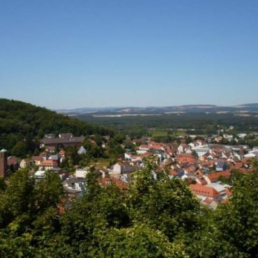 View of a nearby German village from a hill, where you can see the sky, fields, and houses.