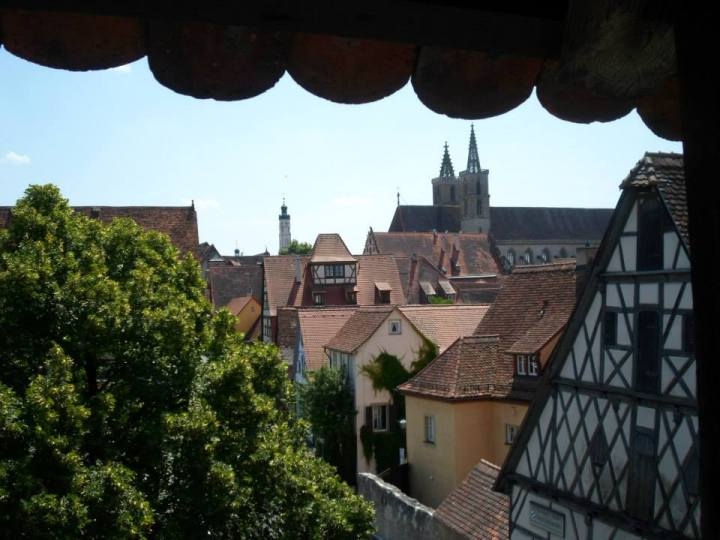 View of the tops of buildings in Rothenburg, Germany.  You see a tree on the left side of the picture, the blue sky, and a small portion of the awning covering the walk path.