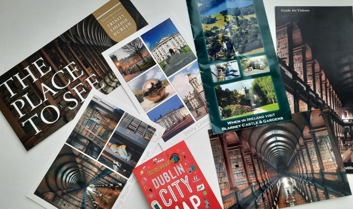 """Scattered postcards, pamphlets, and map of Irish tourist spots in different shapes and sizes. They are on top of a solid white background including visible words of """"Dublin City Map,"""" """"The Place to See,"""" and other Trinity College Dublin and Blarney Castle postcards"""