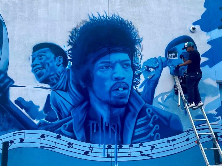 image of Alfredo Pena painting Leon bridges on Blues Alley mural.