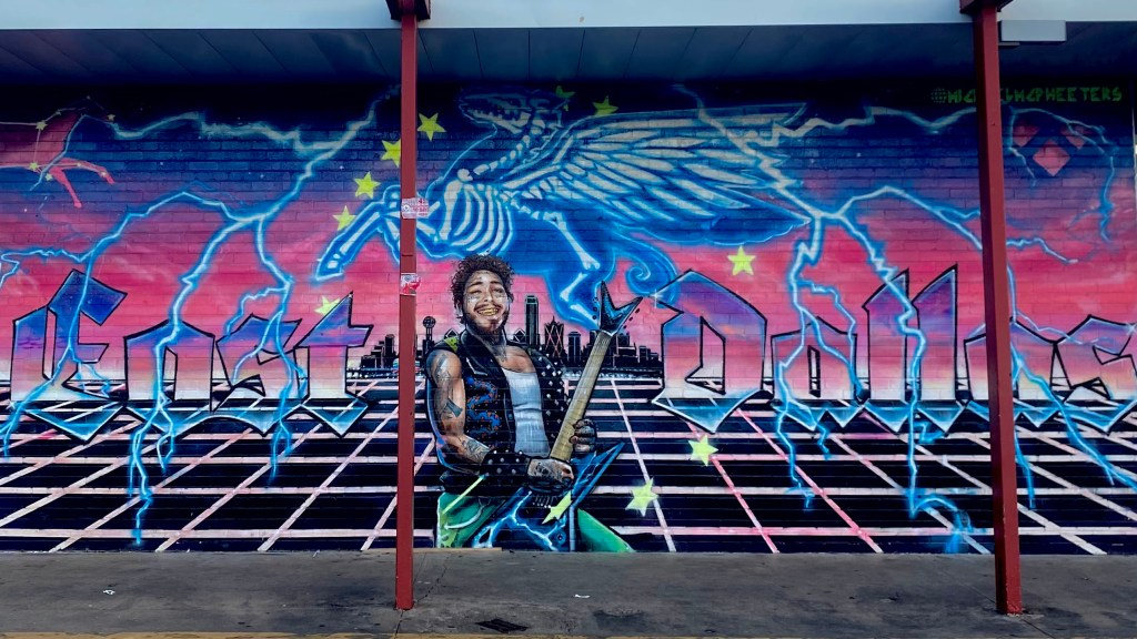"""painting of post Malone in front of Dallas skyline, with """"East Dallas"""" painted on each side of him."""