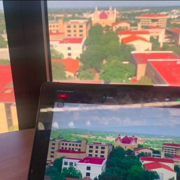 On a round brown table on the 7th floor in alkek library, a standard sized iPad has a zoom call started on it. In the zoom call, the screen is of central Texas State University's campus and features Old Main as a focal point. Behind the table, there is a large window. The view is also of central Texas State University's campus, featuring Old Main.