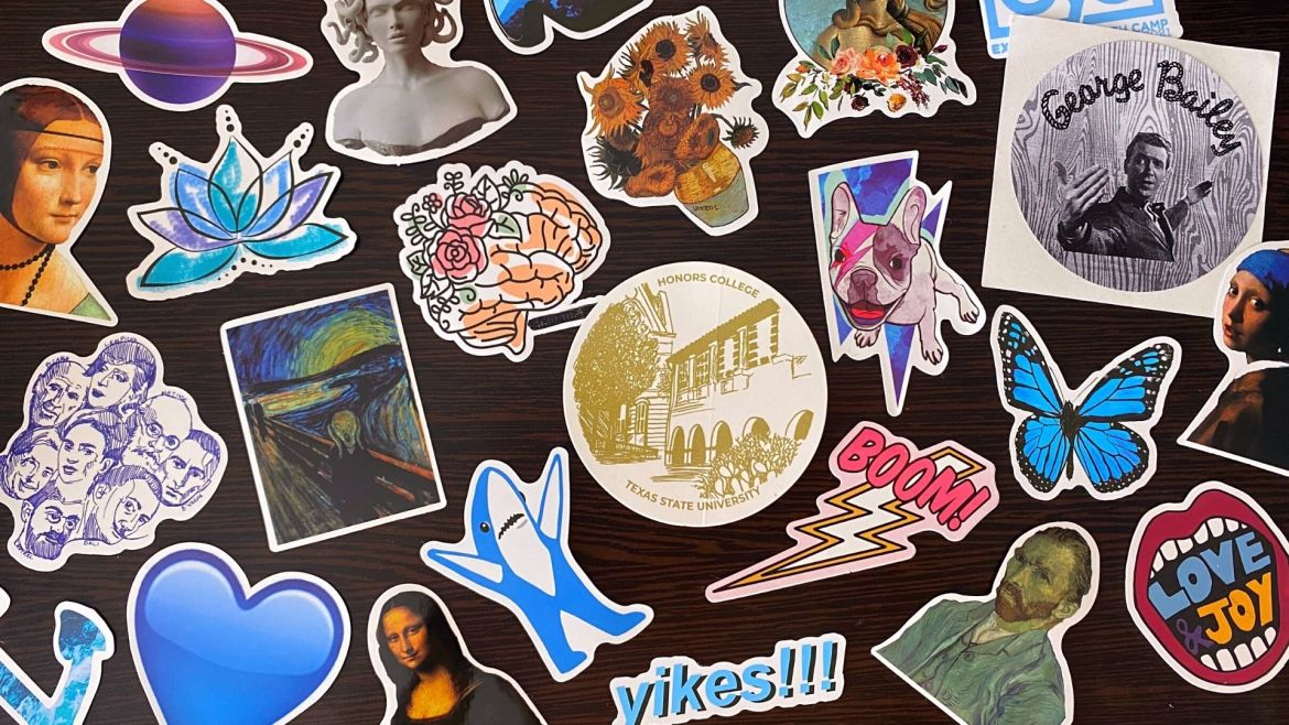 """Photo of various stickers organized in a collage on a table. Stickers include from left to right The Lady With an Ermine by Da Vinci, illustrated portraits of classic artists, a purple planet resembling Saturn, a blue heart Apple emoji, a line drawing of a lotus flower, The Scream by Munch, a marble bust of Medusa, Mona Lisa by Da Vinci, an illustrated human brain with roses, a Super Bowl shark, a golden illustration of the Texas State Honors College, Arles Sunflowers by Van Gogh, blue text reading """"yikes"""" with three exclamation points, a lightning bold with text reading """"boom"""", a white bulldog with a painted pink lightning bolt on its face in front of a blue lightning bolt, a circle portrait of The Birth of Venus by Botticelli with roses underneath, Self Portrait by Van Gogh, a Blue Morpho Butterfly, a greyscale circle sticker reading """"George Bailey"""" with character from It's a Wonderful Life, open mouth with red lips inside reading """"love and joy"""" and Girl with a Pearl Earring by Vermeer."""
