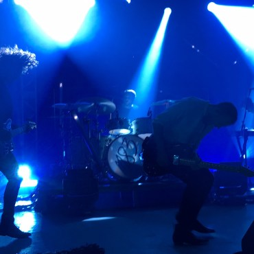 he photo is a live performance from M83 at the venue Stubbs in Austin, Texas showing the lead musician Anthony Gonzalez playing bass along with his guitarist, keyboardist and drummer with dark blue mood light.