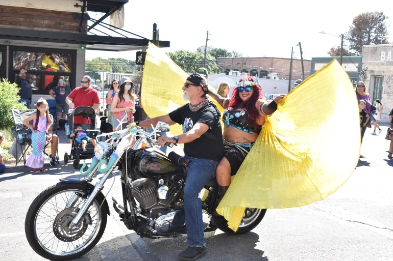 A woman and a man on a motorcycle come down the street during the parade. The man has a black leather jacket and the woman seated behind him has long yellow wings that she is displaying proudly.