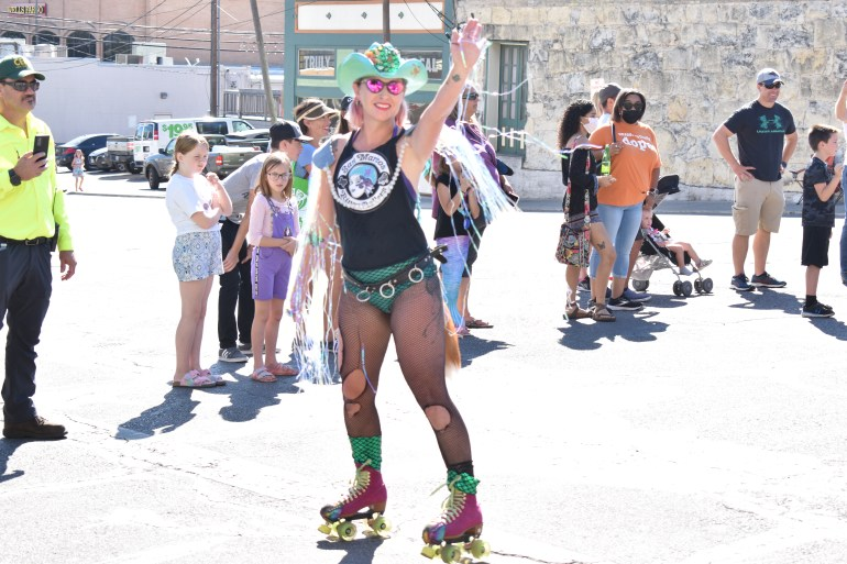 A woman on rollerblades skates down the street in her roller derby outfit, waving to the crowd.