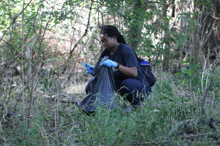 A Texas State student squatting down and picking up trash near Purgatory Creek in Rio Vista Park. They are holding a trash bag in one hand and a piece of trash in the other.