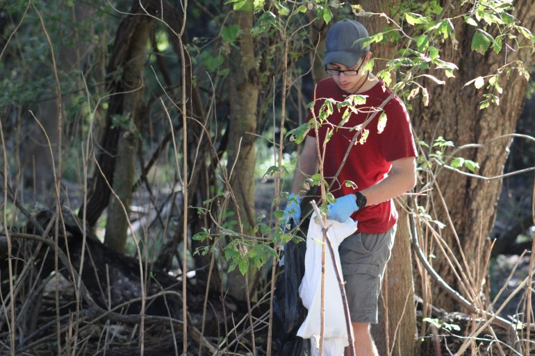A Texas State student looking for litter near Purgatory Creek in Rio Vista Park. They are holding a trash bag in one hand.